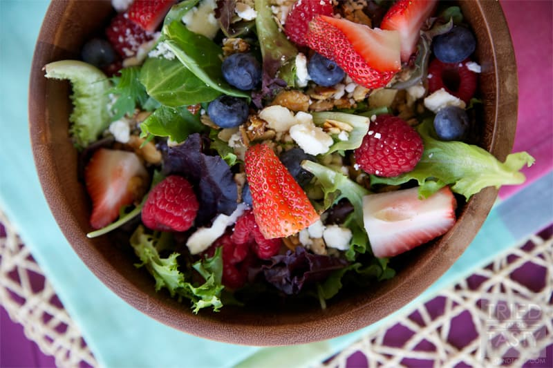 Very Berry Salad with Honey Sweetened Raspberry Vinaigrette // The perfect way to welcome summer. All of your favorite berries on top of a bed of greens sprinkled with feta cheese and candied almonds. Drizzled with a fantastic vinaigrette. | Tried and Tasty