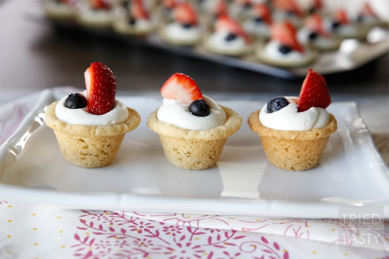 Red White & Blue Strawberry Blueberry Sugar Cookie Cups with Coconut Cream Cheese Filling // These scrumptious little treats are perfect party poppers! They are mini, fit right in the palm of your hand, and will be gobbled up in no time. With the tiniest hint of coconut, you'll be left wanting more! | Tried and Tasty