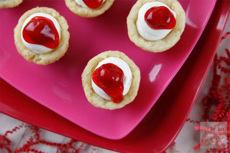 Mini Cherry Cheesecake Sugar Cookie Cups // These delicious little bite-sized bits of heaven are perfect for Valentine's Day! They are mini, fit right in the palm of your hand, and will be gobbled up in no time. With the tiniest hint of coconut, you'll be left wanting more! | Tried and Tasty