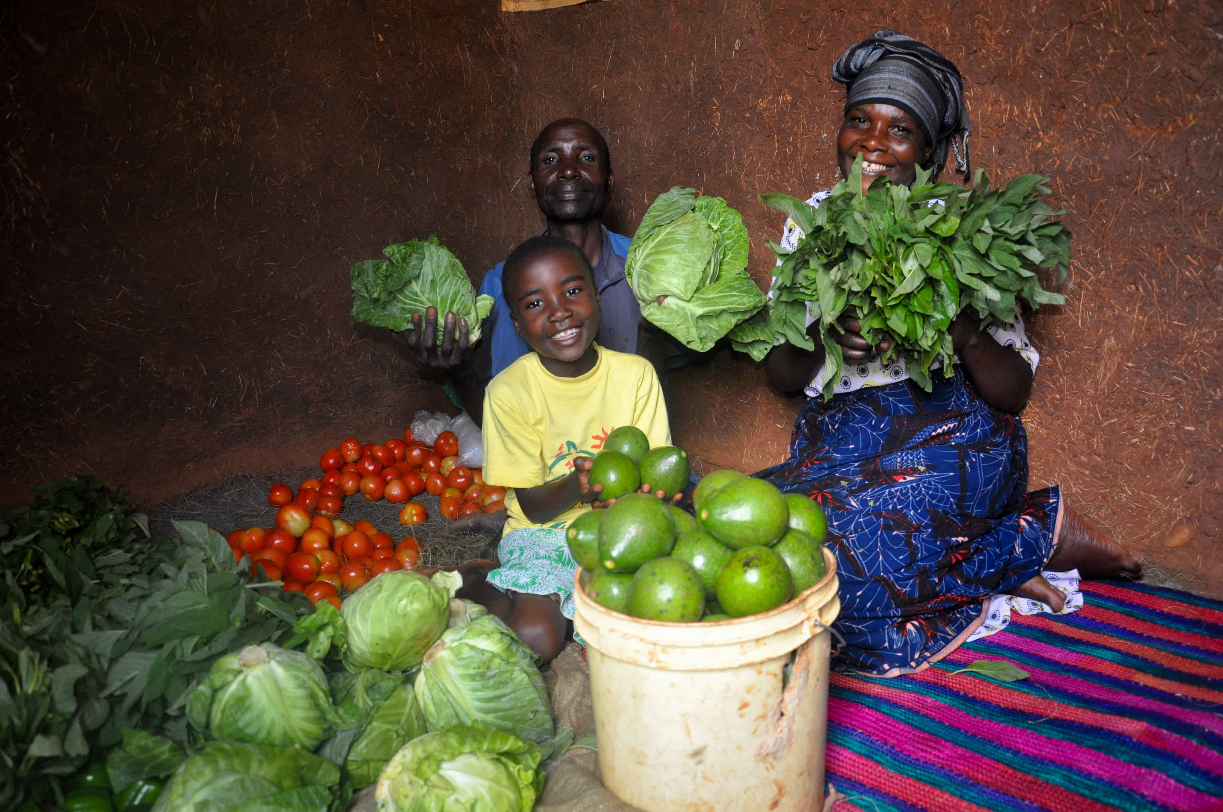A World Vision Tanzania sponsored child Vanessa (6) (centre) is food secured as she holds their horticultural harvests with her parents