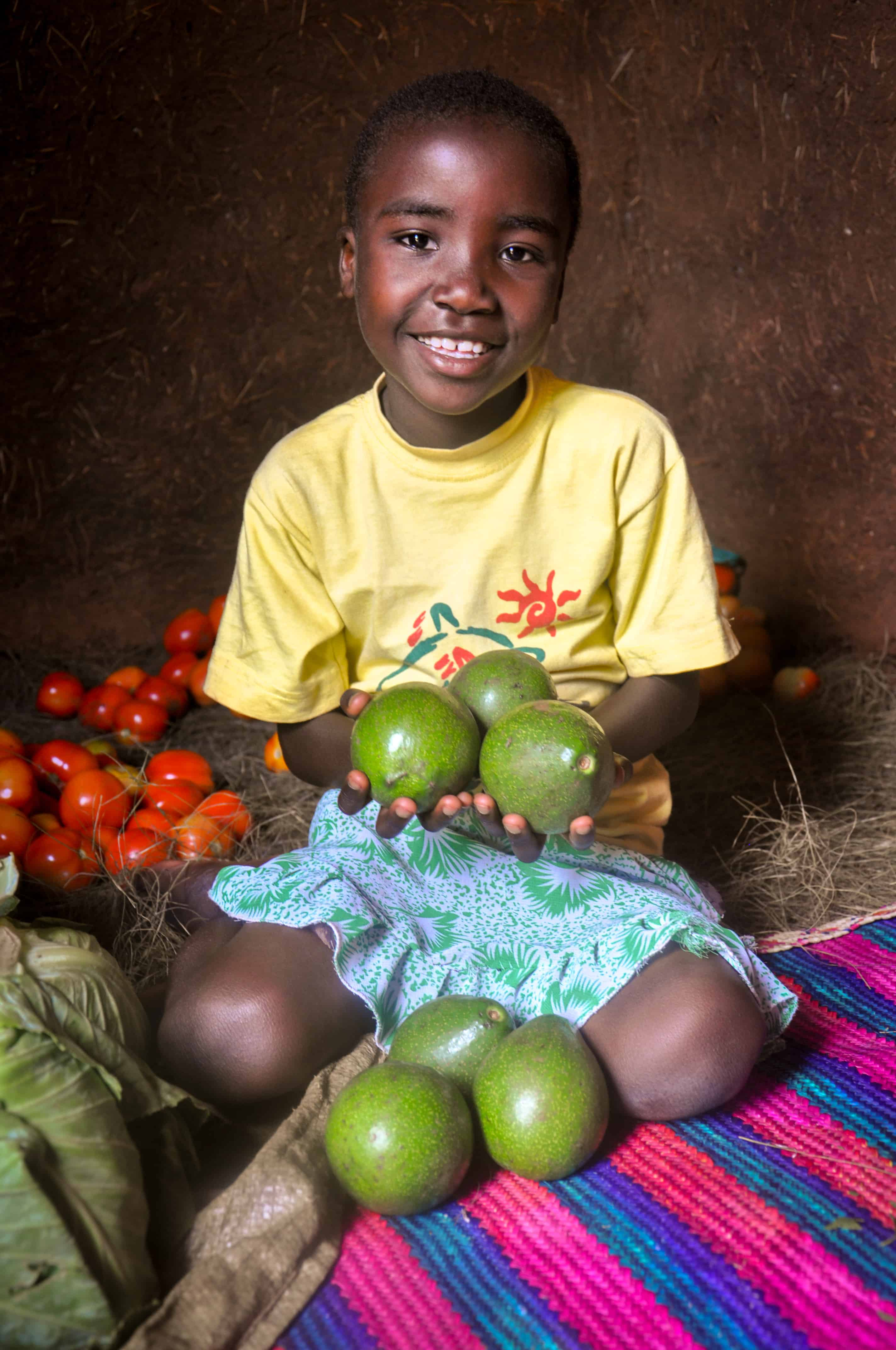 A World Vision Tanzania sponsored child Vanessa (6) happily holding avocadoes which shows food security at her home in Kitoko village located in north western Tanzania