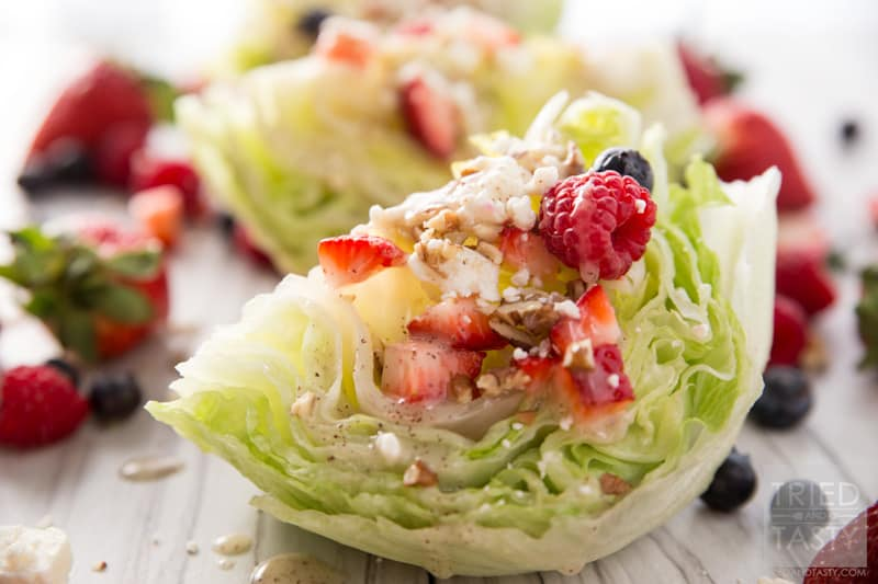 Mixed Berry Wedge Salad // Seve this at your next BBQ! You only need a handful of ingredients including: fresh lettuce, in-season berries, dressing and cheese. The crowd will go nuts with the stunning side dish! | Tried and Tasty